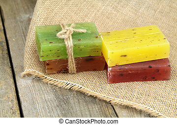 Colorful natural herbal soaps on linen sack. - Colorful...