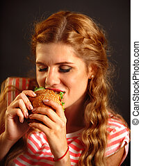 Woman eating fast food . Girl enjoying delicious hamburger.