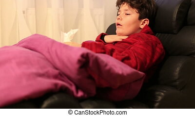 Child at home sick with flu lying on bed and resting - Young...