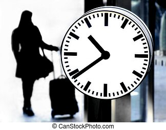 Station clock and a passenger waiting with baggage close up...