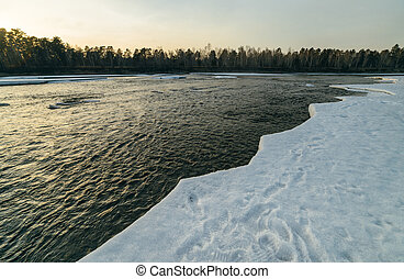 Winter sunset in river.