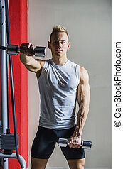 Muscular young man working out in gym with dumbbells