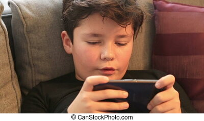 Child with smartpnone gaming at home - Child using mobil...