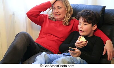 Happy mother and son watching tv at home