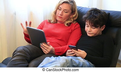 Mother and son using digital equipment