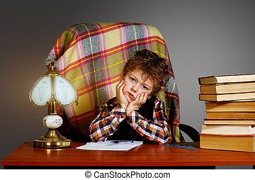A tired boy at the table with books. Preschool education