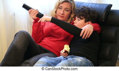 Mother and son watching tv at home