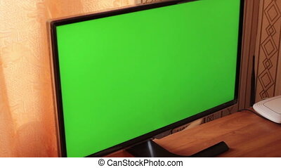 slowly approaching the monitor with a green screen.