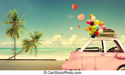 Vintage pink classic car with heart colorful balloon on beach blue sky