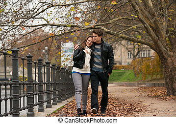 Happy young Couple in Autumn Park. Fall. Yellow Trees and...
