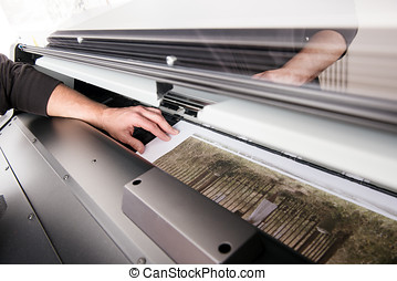 Printing out graphic photo on wide printer - Hand of man...
