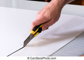 Cutting paper with utility knife - Close-up man hand with...