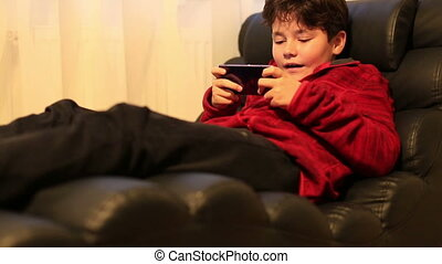 Portrait of young boy using smartphone at home - Young boy...