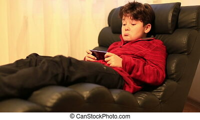 Young burunette child with smart phone at home - School...