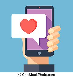Hand holding smartphone with heart emoji message on screen,...