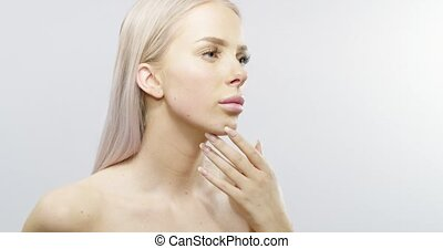Slow motion studio portrait of a blonde touching her skin -...
