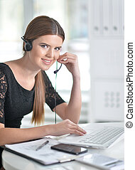 Young woman in headset using laptop