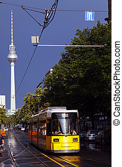 Tram on Street with Fernsehturm - A yellow tram riding on a...