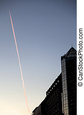 Dawn Building and Airplane Smoke Trail - A modern building...