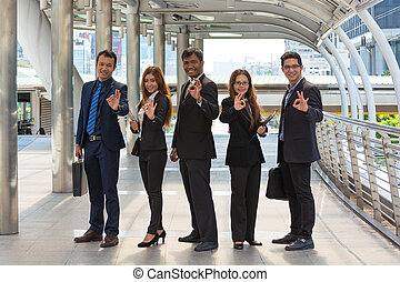 Energetic Young Businesspeople, three businessmen and two Businesswomen showing ok symbol