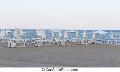 wind on empty beach and empty chaise-longue - wind on empty...