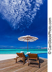 Sun umbrellas and wooden beds on tropical beach with the best view