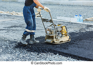 Worker use vibratory plate compactor compacting asphalt at...