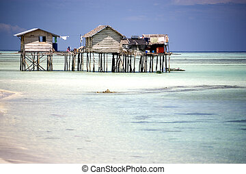 Huts on Stilts - Image of huts on stilts with clear water in...