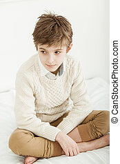 Thoughtful young boy sitting on his bed