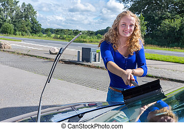Young dutch woman washing car windshield