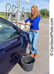 Young dutch woman washing car window