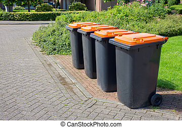 Row of dutch grey waste bins along street