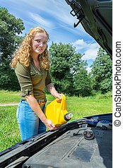 Young caucasian woman fills car motor with oil - Young dutch...
