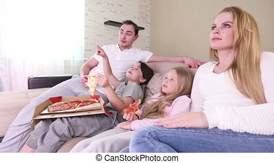 Family watching TV - Young parents and their children are...