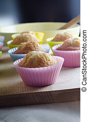 Freshly Baked Cupcakes Cooling on Wooden Chopping Board -...