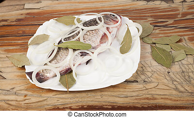 Fish on a white plate on a wooden background