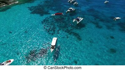 Racha Island Beach. Thailand, Phuket. Yachts , Catamarans and Boats sailing in crrystal clear blue water of ocean. Flying from beach to ocean. Look down. Aerial view. 4K.