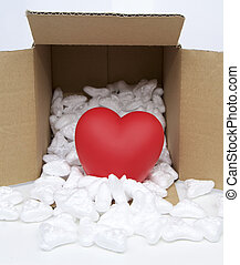 Red heart in mail package box with styrofoam close up image