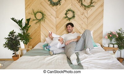 Happy handsome young father lying on bed and playing with his son