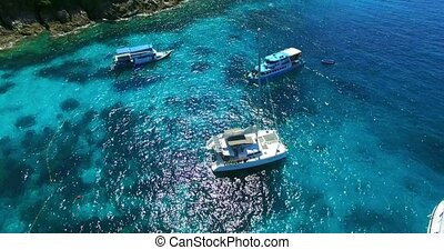 Racha Island Beach. Thailand, Phuket. Yachts , Catamarans and Boats sailing in crrystal clear blue water of ocean. Take off from ocean to sky. Aerial view. 4K.