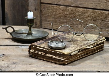 antique book with accessories on wooden background