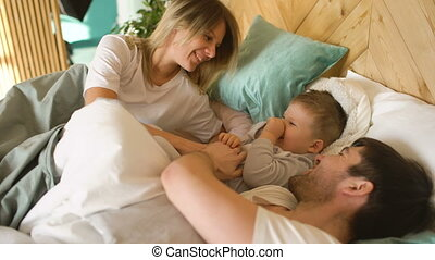 Happy family wake up and play in bed at home indoors