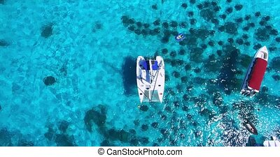 Racha Island Beach. Thailand, Phuket. Yachts , Catamarans and Boats sailing in crrystal clear blue water of ocean. Take off from ocean to sky. Catamaran in center of view. Aerial view.