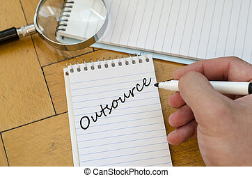 Outsource concept on notebook - Outsource text concept write...