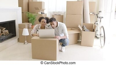 Young black couple moving into their new home sit beside...