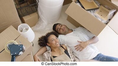 Attractive couple lying on the floor of their home -...