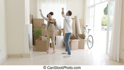 Young couple dancing for joy in the living room of their new...