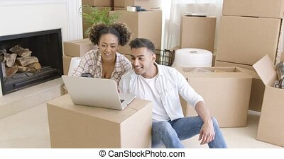Happy couple using laptop in their new apartment - Happy...