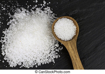 Rock Salt and wooden spoon on black stone background. Macro...
