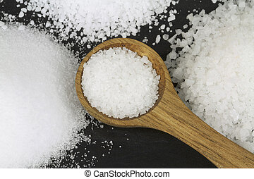 Various Salt and wooden spoon on black stone background....